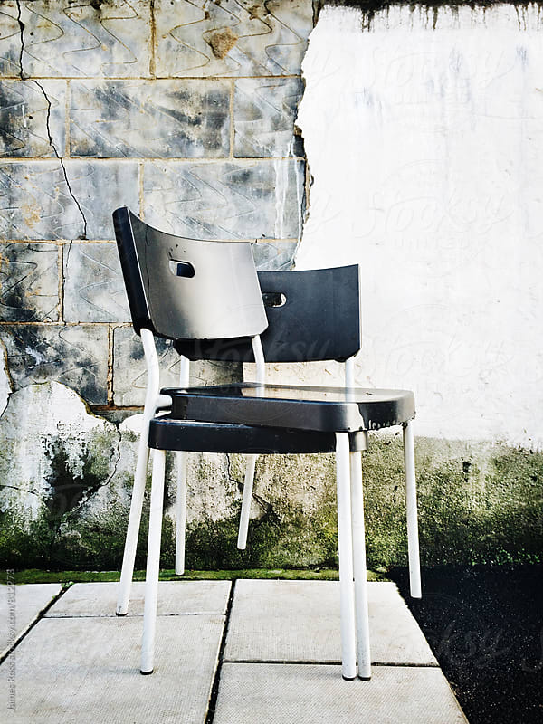 Two stacked chairs against a textured wall by James Ross for Stocksy United