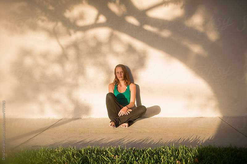 Teenage Girl Sitting Up Against Wall With Tree Shadows by Dina Giangregorio for Stocksy United