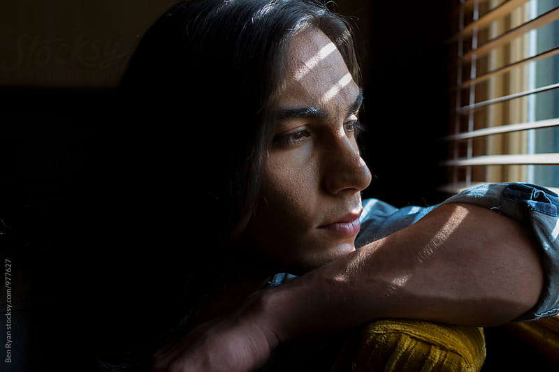 Portrait of young middle eastern man looking out window with bands of light on face by Ben Ryan for Stocksy United