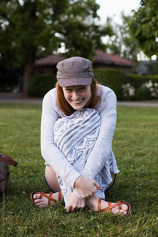 Smiling young woman sitting on the grass in the park by michela ravasio for Stocksy United