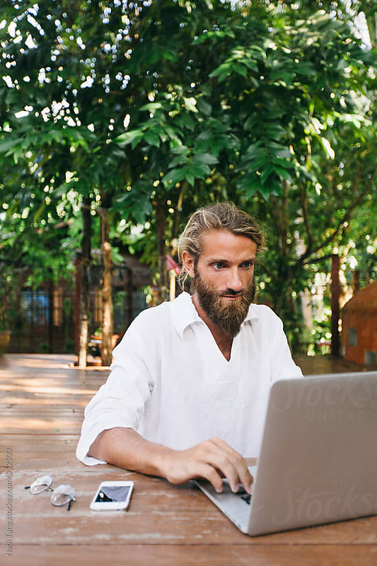 Young man working on computer in the garden by Nabi Tang for Stocksy United