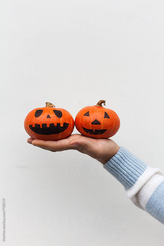 Male hand holding two Halloween pumpkin in front of a white wall by Marija Mandic for Stocksy United