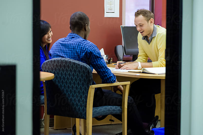 Group of employees working in a busy office by Jen Grantham for Stocksy United
