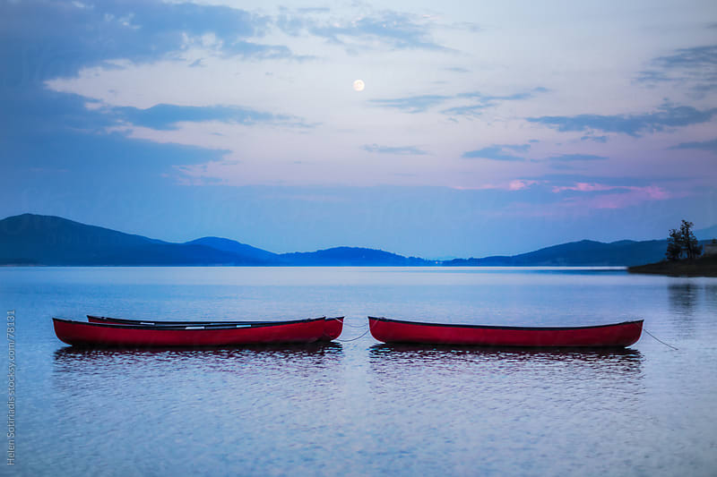 Canoes on a lake under the moon by Helen Sotiriadis for Stocksy United