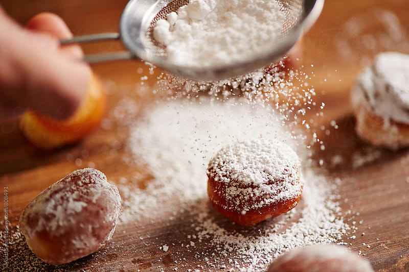 Pouring icing sugar on donut holes by Martí Sans for Stocksy United