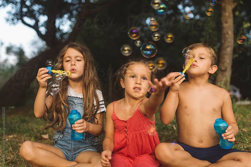 Children playing with bubbles. by Dejan Ristovski for Stocksy United