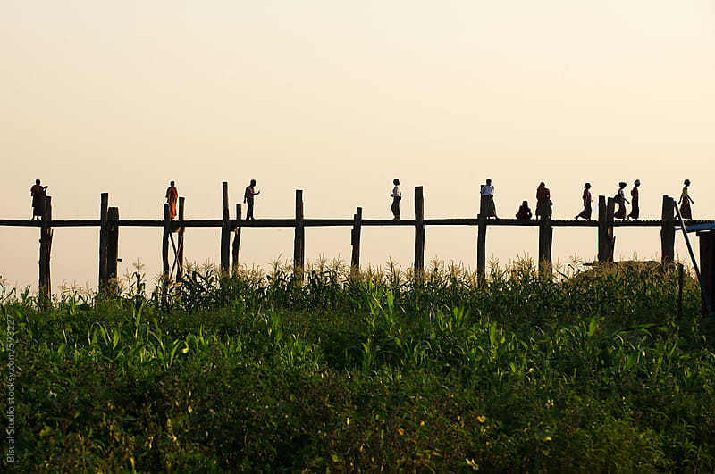 Silhouette of people walking by a long wooden bridge at sunset by Bisual Studio for Stocksy United