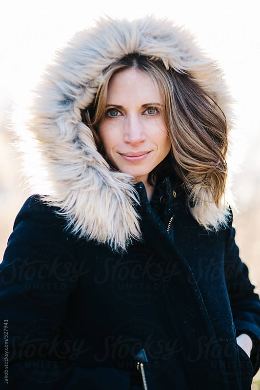Portrait of a beautiful woman with a fur trim hood over her head by Jakob for Stocksy United