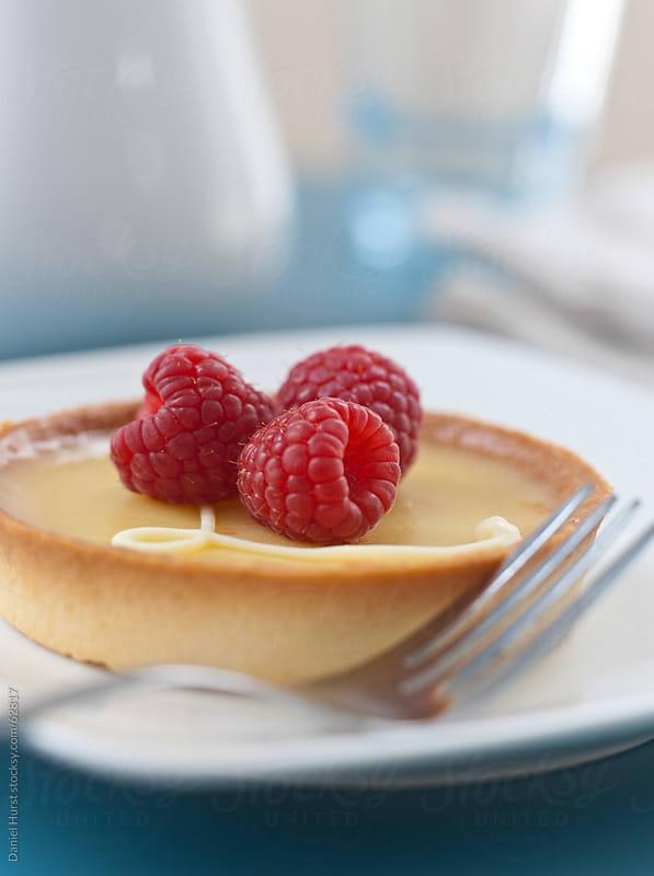 Lemon tart with fresh red raspberries by Daniel Hurst for Stocksy United