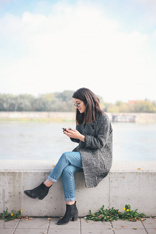 Stylish woman browsing on her mobile phone sitting on a quay  by Marija Mandic for Stocksy United