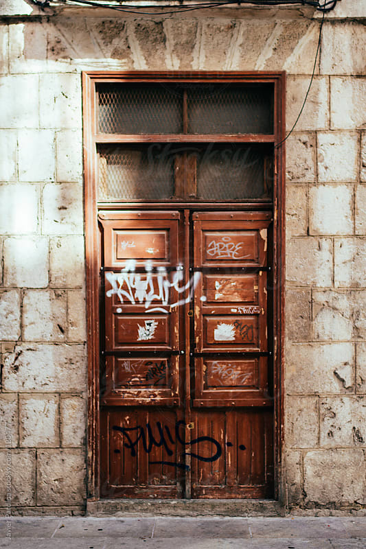 Old red door with graffiti on the street by Javier Pardina for Stocksy United