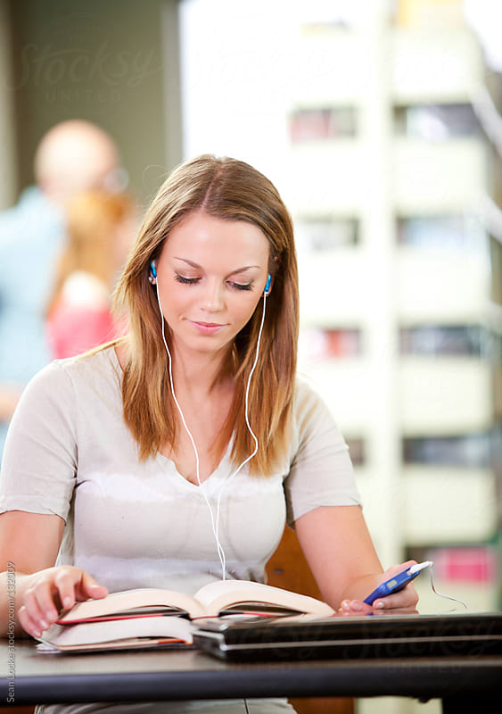 Library: Teen Listens to Music While Doing Homework by Sean Locke for Stocksy United