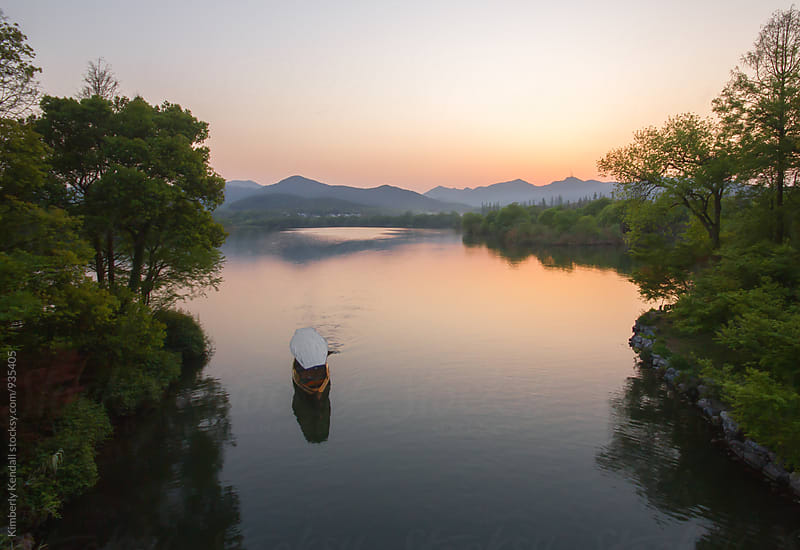 Small boat on lake in Hangzhou China by Kimberly Kendall for Stocksy United