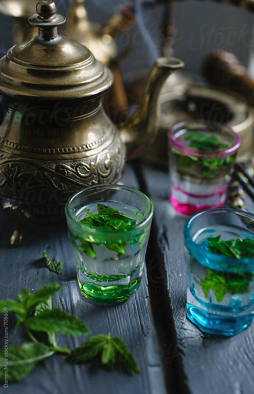 Mint tea in glasses on a table with teapot and incense burning in background. by Darren Muir for Stocksy United