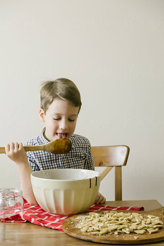 Boy licks spoon by Kirsty Begg for Stocksy United