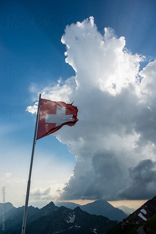 Swiss national flag in high alps by Peter Wey for Stocksy United