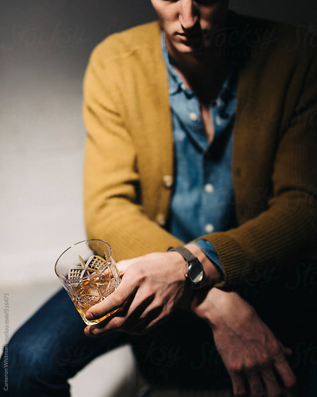 Somber man with a glass of whiskey by Cameron Whitman for Stocksy United