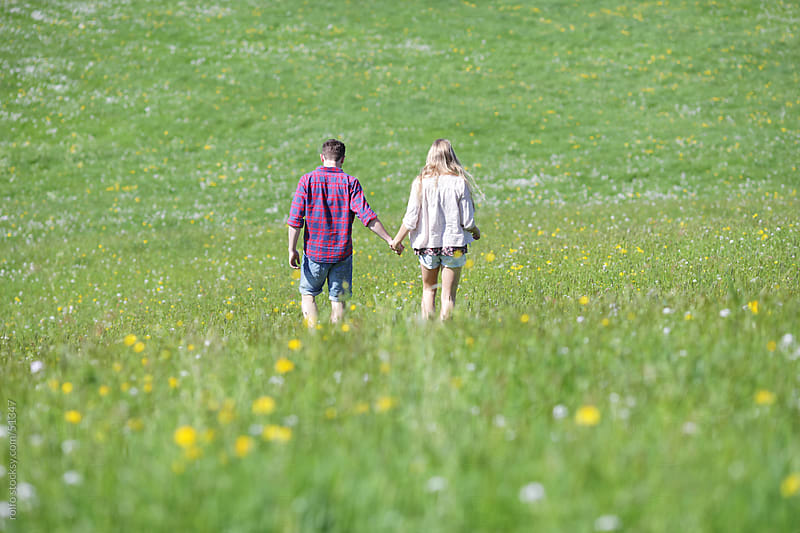 young couple big green meadow  by rolfo for Stocksy United