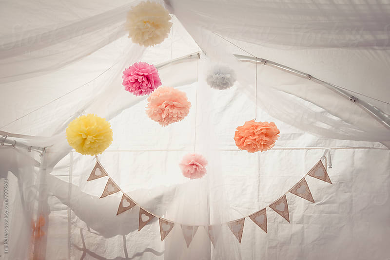 Wedding decoration, colorful pompons hanging in a white tent by Ina Peters for Stocksy United
