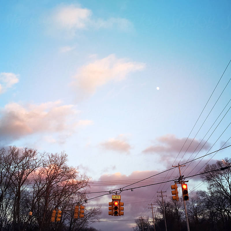 Red Stop Lights Against An Autumn Sunset With A Tiny Moon by ALICIA BOCK for Stocksy United