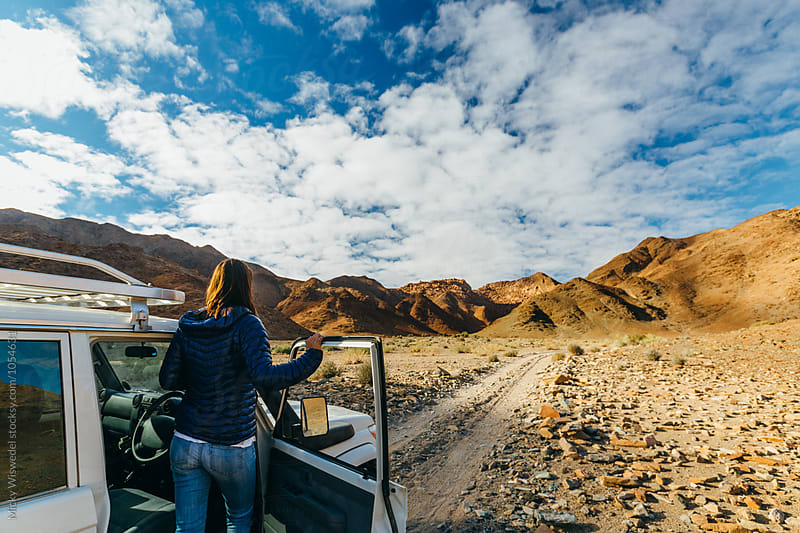 Woman on a roadtrip in a rugged desert by Micky Wiswedel for Stocksy United