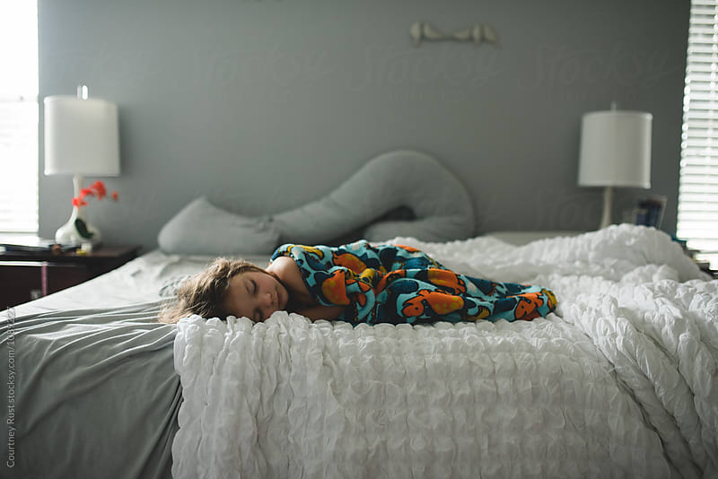 Child sleeping on large bed by Courtney Rust for Stocksy United