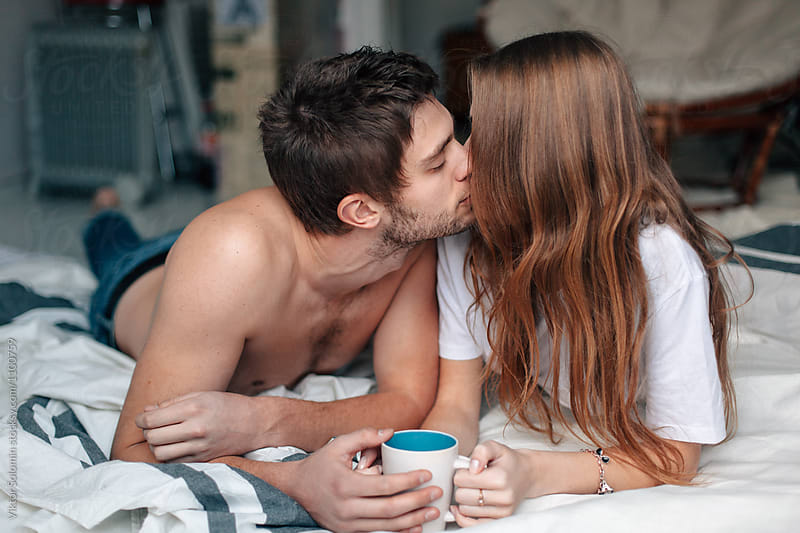 Young couple lying in bed and drinking coffee, kissing by Viktor Solomin for Stocksy United