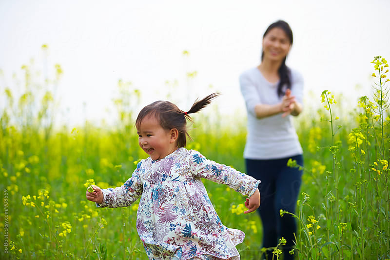 mother and little girl in the spring field by cuiyan Liu for Stocksy United