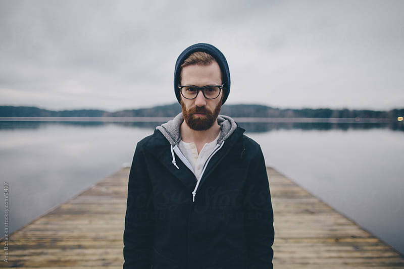 A portrait of a man standing on a dock by Ania Boniecka for Stocksy United