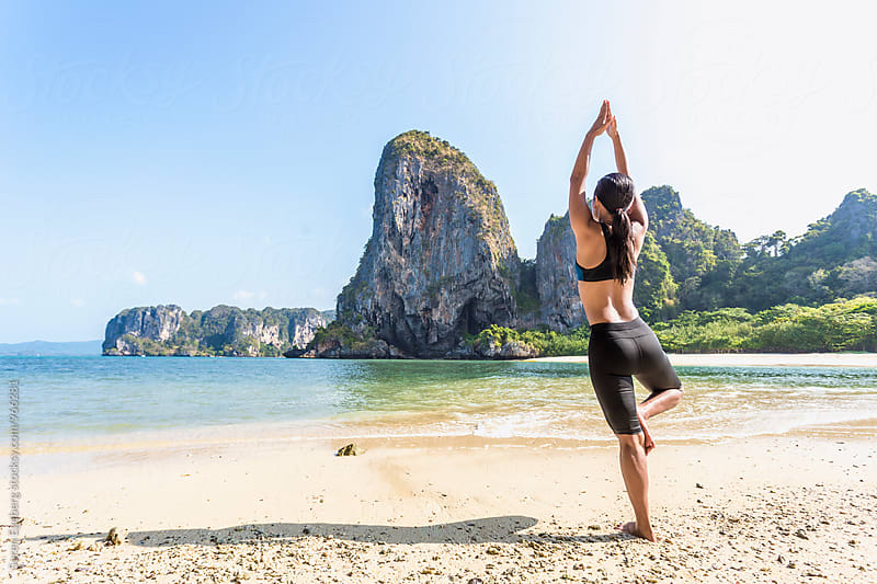 Asian fitness woman doing yoga alone on the beach by Søren Egeberg Photography for Stocksy United