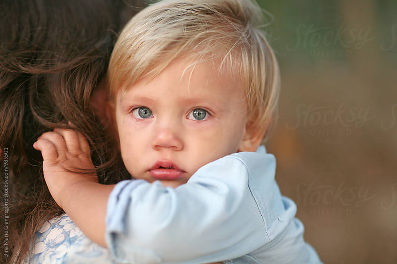 Blonde Hair Blue Eyed Toddler With Teary Eyes being Held by Dina Giangregorio for Stocksy United