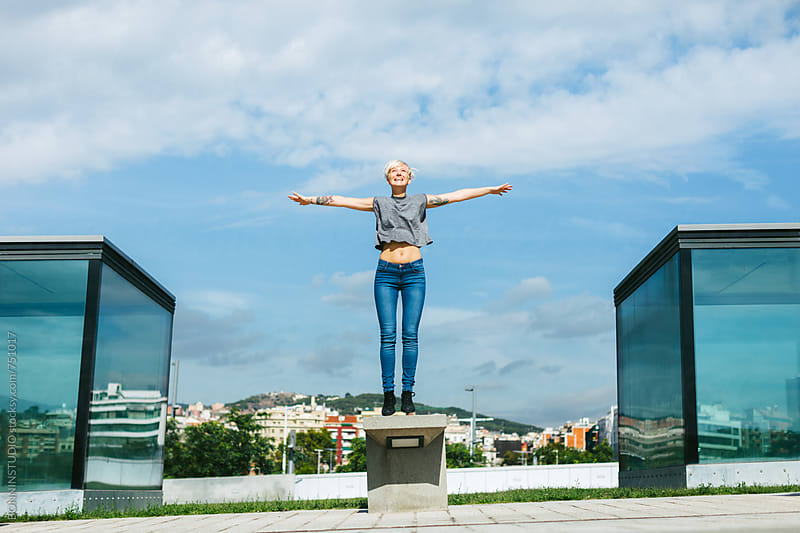 Happy young woman jumping in the city. by BONNINSTUDIO for Stocksy United