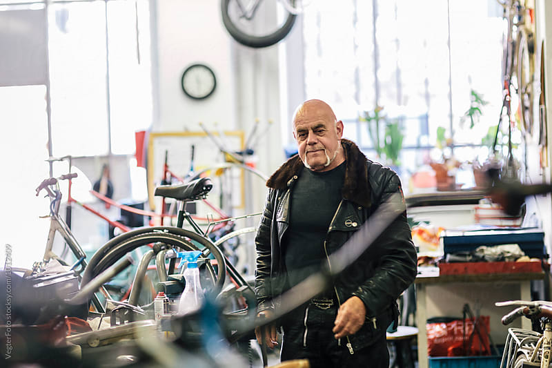 Senior Bicycle Mechanic walking towards workbench by VegterFoto for Stocksy United