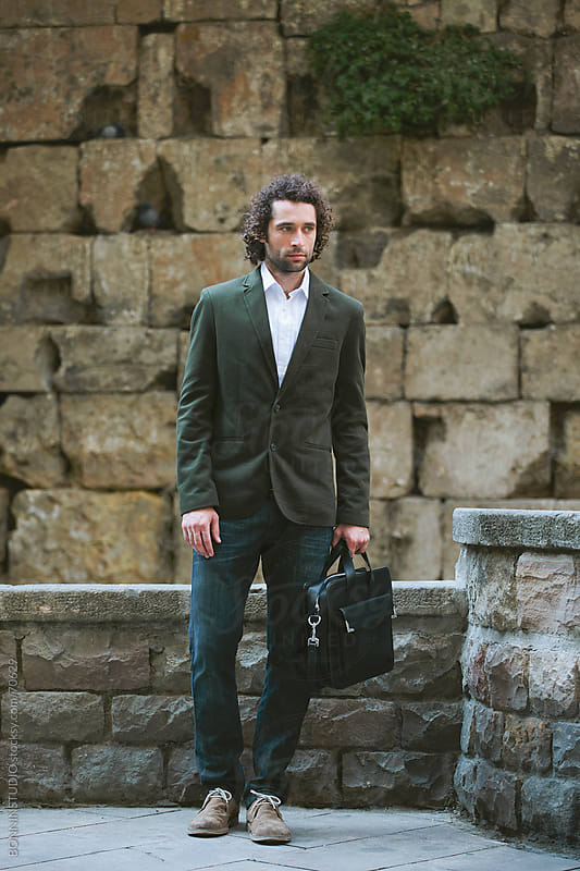 Young modern businessman with briefcase standing on Barcelona street. El gotic. by BONNINSTUDIO for Stocksy United