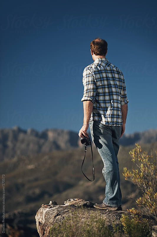 man with camera in mountains by Daxiao Productions for Stocksy United