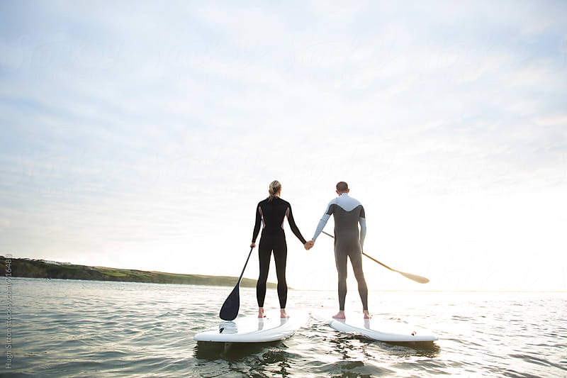 Couple paddle boarding at sunset. by Hugh Sitton for Stocksy United