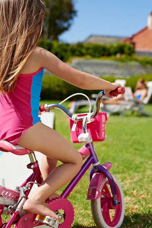 Cute girl on pink bicycle in yard by Aila Images for Stocksy United