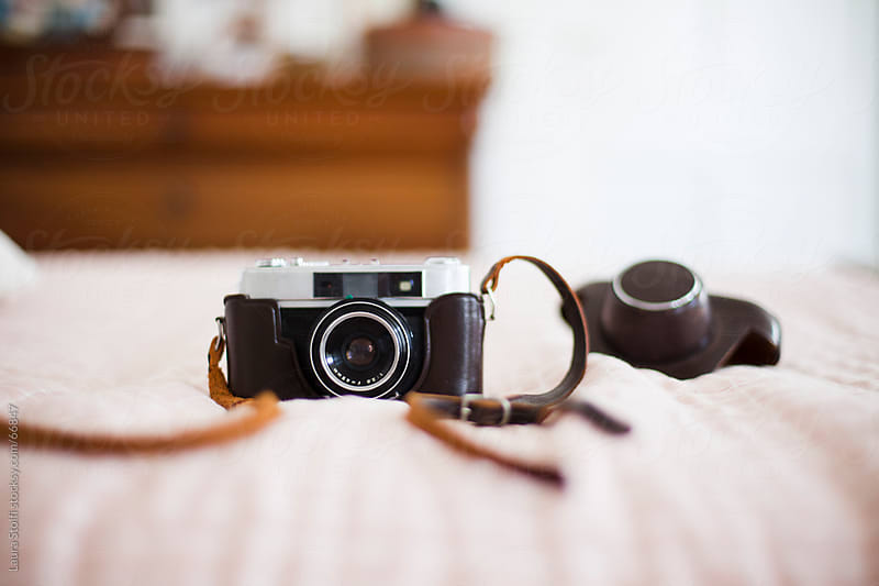 Old 35mm camera and leather case on quilt on bed in sunny bedroom by Laura Stolfi for Stocksy United