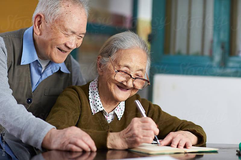 senior asian couple writing by Bo Bo for Stocksy United