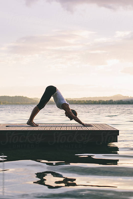 Woman doing yoga outdoors by michela ravasio for Stocksy United