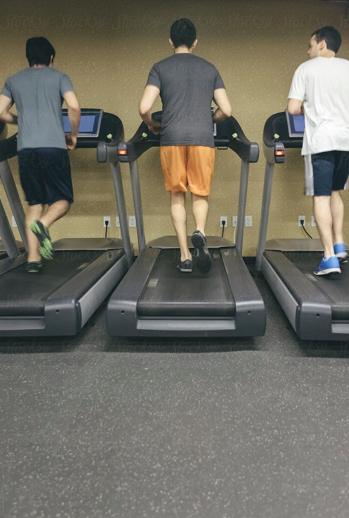 Latino friends and roommates running on threadmill in gym for