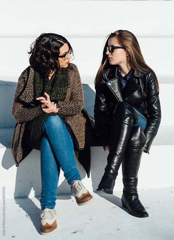 Two friends sitting and having a conversation by Kate & Mary for Stocksy United