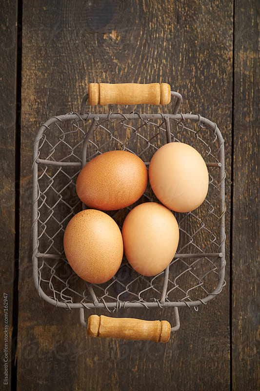 Chicken eggs  in a basket by Elisabeth Coelfen for Stocksy United
