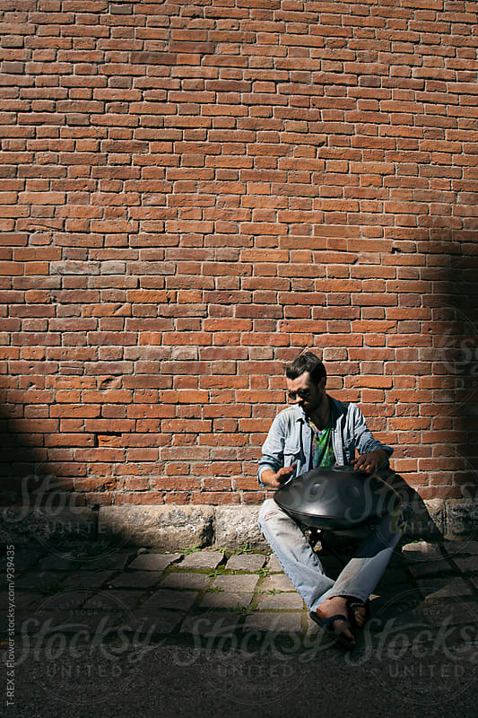 Man in sunglasses playing hang drum by Danil Nevsky for Stocksy United