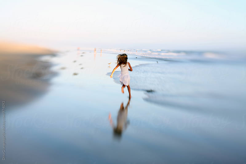 Little Girl Running Away On Reflective Beach by Dina Giangregorio for Stocksy United