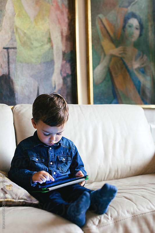 Kid using his digital tablet at home. by BONNINSTUDIO for Stocksy United