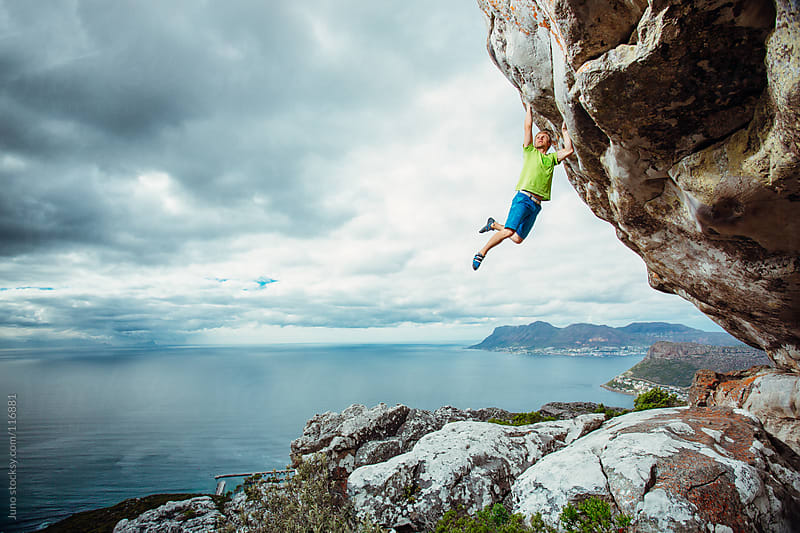 Young man rock climbing on an overhanging cliff by Micky Wiswedel for Stocksy United