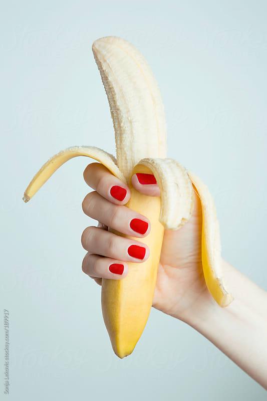 female hand holding a peeled banana by Sonja Lekovic for Stocksy United