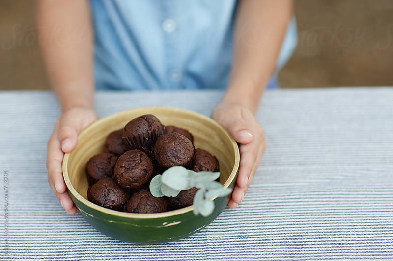 Close up of a child with a bowl full of chocolate muffins by Miquel Llonch for Stocksy United