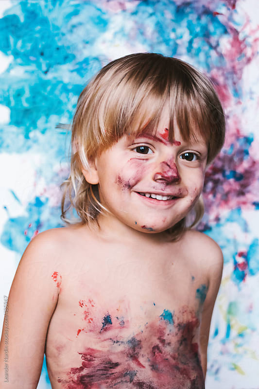 colorfully painted toddler with outstretched tongue in front of colorful canvas by Leander Nardin for Stocksy United